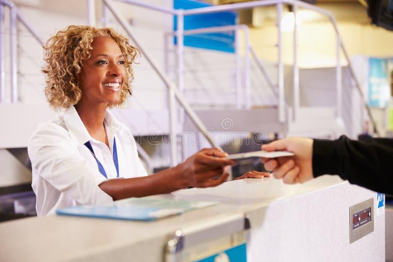 Προσωπικό στον έλεγχο αερολιμένων στο γραφείο που δίνει το εισιτήριο στον επιβάτη στοκ εικόνα με δικαίωμα ελεύθερης χρήσης