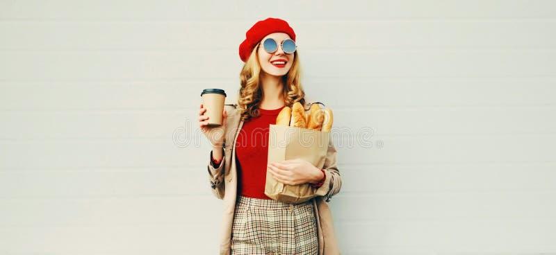 Προσωπογραφία όμορφη χαμογελαστή γυναίκα που κρατά κούπα καφέ, σακούλα για ψώνια με μακριά λευκή μπαγκέτα ψωμιού πάνω από το λευκ στοκ φωτογραφία