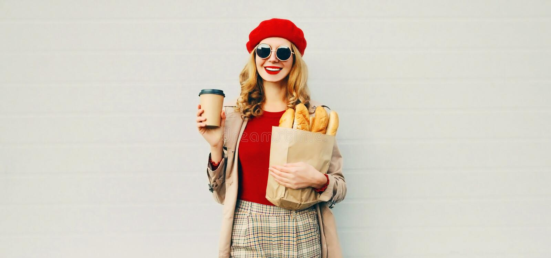 Προσωπογραφία όμορφη χαμογελαστή γυναίκα που κρατά κούπα καφέ, σακούλα για ψώνια με μακριά λευκή μπαγκέτα ψωμιού πάνω από το λευκ στοκ εικόνες