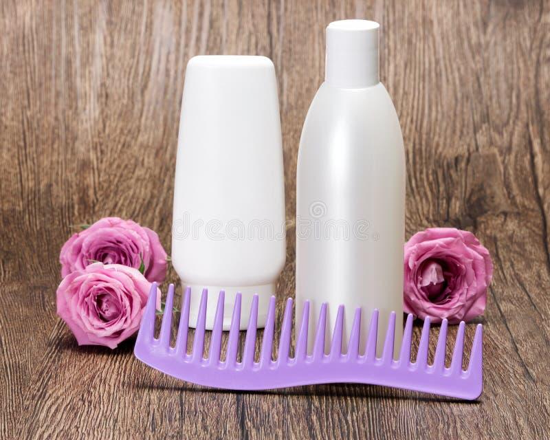 Προϊόντα και χτένα ομορφιάς τρίχας με τα τριαντάφυλλα στοκ εικόνες με δικαίωμα ελεύθερης χρήσης