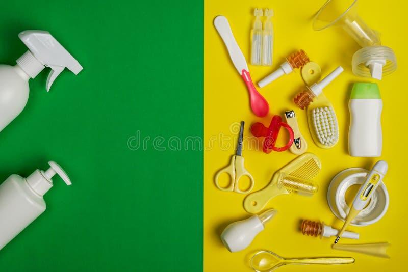 Προϊόντα πρώτης ανάγκης καλλωπισμού μωρών και αποστειρώνοντας μπουκάλι στο διπλός-χρωματισμένο υπόβαθρο στοκ εικόνες