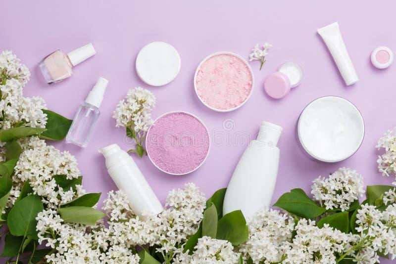 Προϊόντα φροντίδας δέρματος στο πορφυρό υπόβαθρο με το άσπρο ιώδες άνθος άνοιξη στοκ φωτογραφία με δικαίωμα ελεύθερης χρήσης