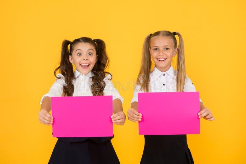 Προώθηση με διαφήμιση Χαρούμενα μικρά παιδιά που δείχνουν ροζ φύλλα χαρτιού για διαφήμιση σε κίτρινο φόντο Μικρό στοκ εικόνα
