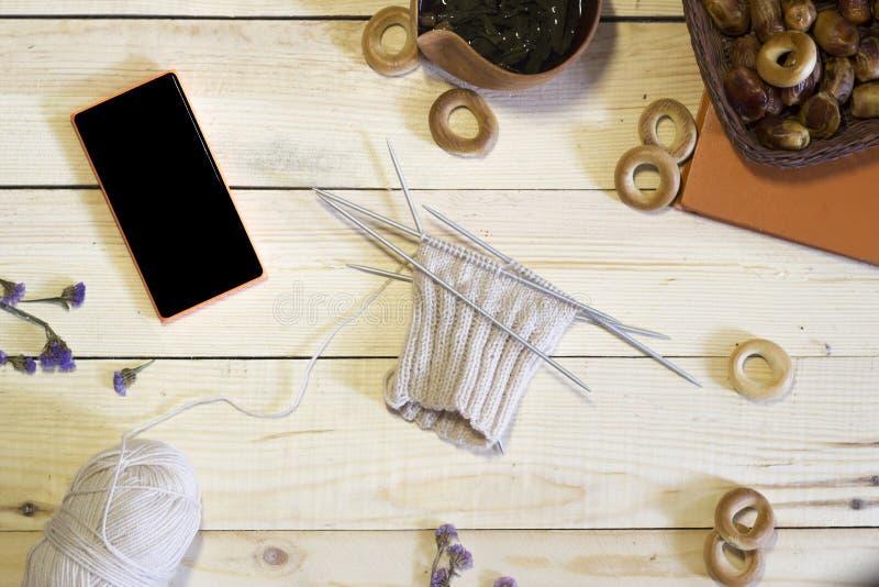 Πρωί για knitter, η σύνθεση του πλεκτού προϊόντος, τηλέφωνο, βιβλίο, τσάι και ξηροί καρποί στο ξύλινο υπόβαθρο στοκ φωτογραφίες