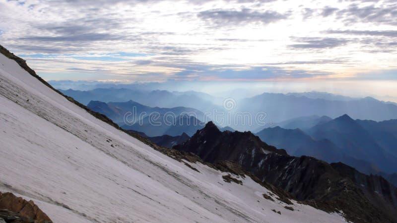 Πρωί και ατμόσφαιρα χαραυγών στις Άλπεις της Ελβετίας με έναν απότομο παγετώνα στο πρώτο πλάνο και τις σειρές των μουντών βουνών  στοκ εικόνες