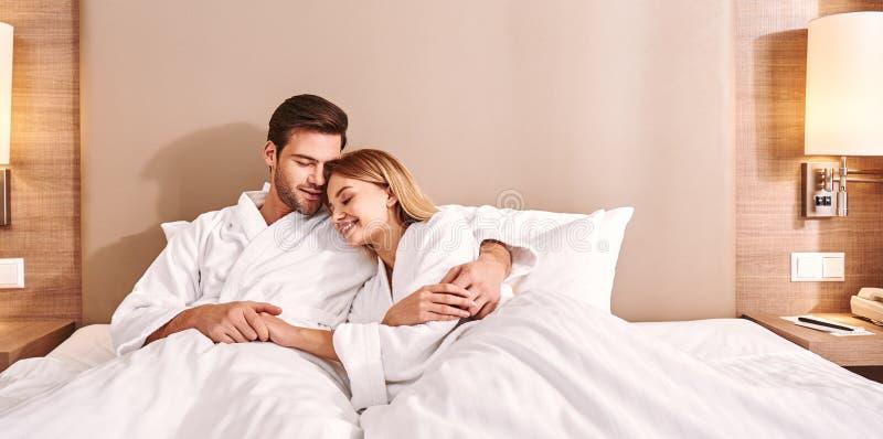 Πρωί με αγαπημένο Το ζεύγος αγκαλιάζει στο κρεβάτι δωματίου ξενοδοχείου στοκ εικόνες