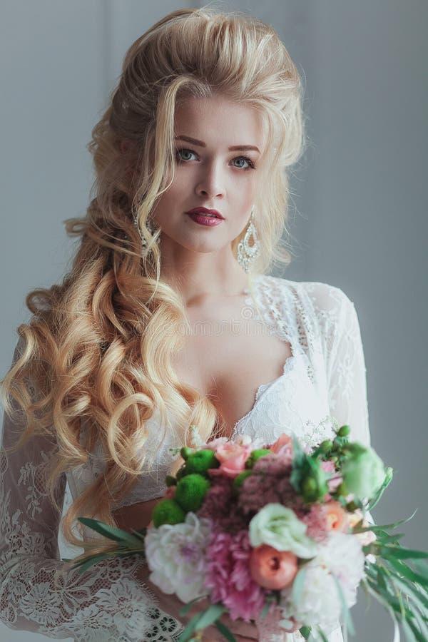 Πρωί της νύφης Όμορφη νέα γυναίκα στην άσπρη ρόμπα που μένει κοντά στο παράθυρο με μια ανθοδέσμη στοκ φωτογραφίες
