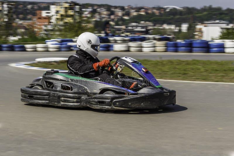 Πρωτάθλημα Karting Ο οδηγός στα karts που φορούν το κράνος, συναγωνιμένος το κοστούμι συμμετέχει στη φυλή kart Το Karting παρουσι στοκ φωτογραφίες με δικαίωμα ελεύθερης χρήσης