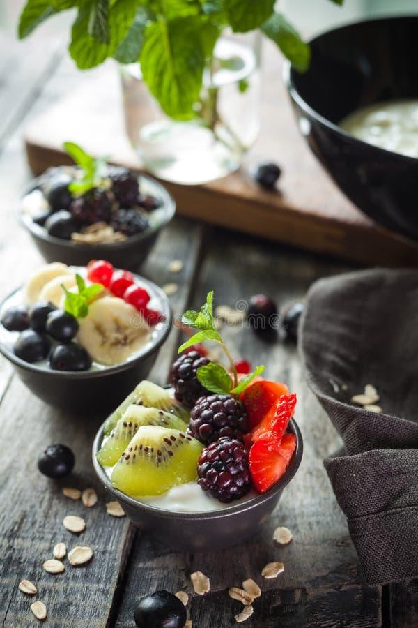 Πρωτεικά ελληνικά γιαούρτια με φρούτα: μπανάνα, μούρα, κίουι στοκ φωτογραφία με δικαίωμα ελεύθερης χρήσης