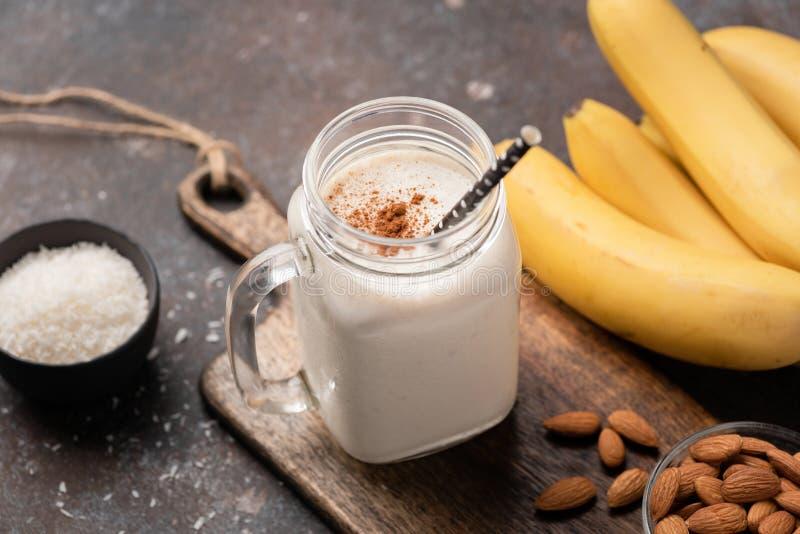 Πρωτεϊνικός καταφερτζής μπανανών ή milkshake με την κανέλα και την καρύδα στοκ φωτογραφία