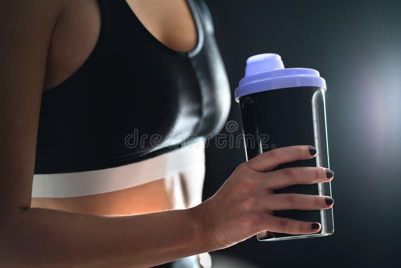 Πρωτεϊνικό κούνημα μετά από την κατάρτιση workout και γυμναστικής Κατάλληλο μπουκάλι εκμετάλλευσης γυναικών του αθλητικού ποτού,  στοκ φωτογραφία με δικαίωμα ελεύθερης χρήσης