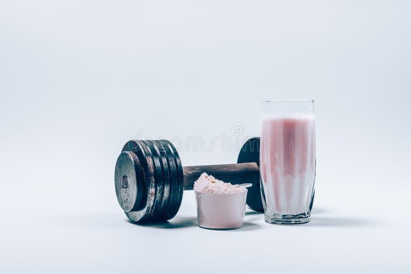 Πρωτεϊνικό κούνημα ορρού γάλακτος σε ένα γυαλί δίπλα στη σέσουλα της σκόνης στοκ εικόνα με δικαίωμα ελεύθερης χρήσης