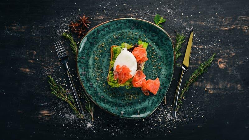 Πρωϊνό Αυγό πουράκι, σολομός σε μαρούλι σε ψωμί τοστ στοκ εικόνες