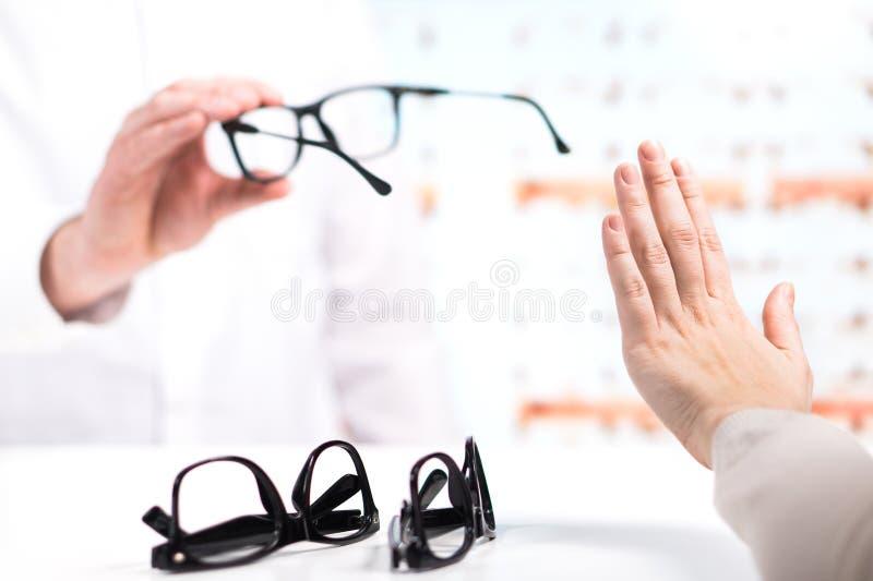 Πρόβλημα στον οπτικό Ο δυστυχισμένος πελάτης αρνείται να προσπαθήσει στοκ φωτογραφία