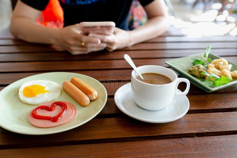 Πρόγευμα, αυγά, λουκάνικα, ζαμπόν και μαύρος καφές στοκ φωτογραφίες