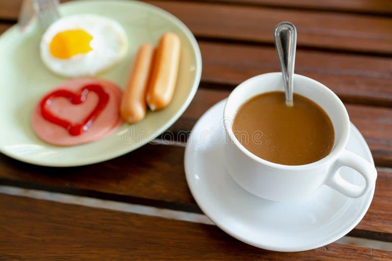 Πρόγευμα, αυγά, λουκάνικα, ζαμπόν και μαύρος καφές στοκ εικόνες