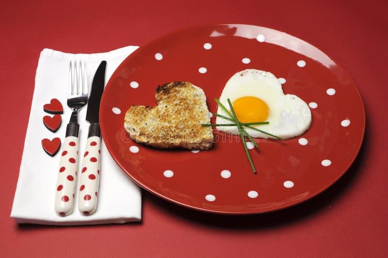 Πρόγευμα βαλεντίνων θέματος αγάπης στο κόκκινο πιάτο σημείων Πόλκα στοκ εικόνες