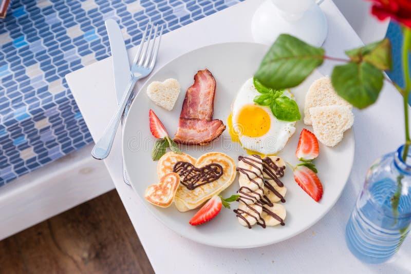 Πρόγευμα ημέρας βαλεντίνων ` s - μπέϊκον, αυγό, τηγανίτα, μπανάνα στοκ εικόνα