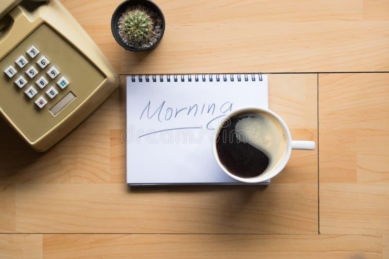 Πρόγευμα και φλιτζάνι του καφέ καλημέρας στον πίνακα εργασίας στοκ εικόνα