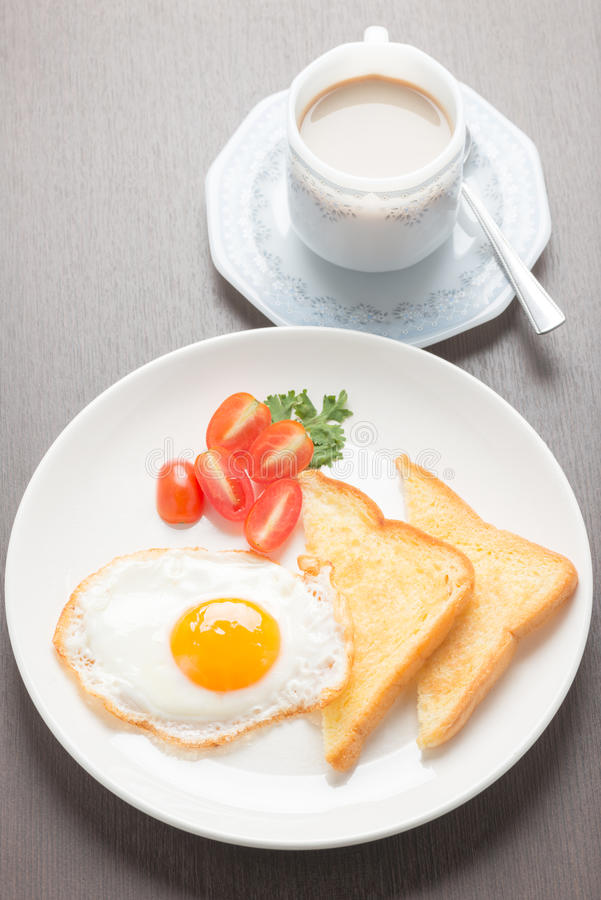 Πρόγευμα με τα τηγανισμένες αυγά και τις φρυγανιές στον ξύλινο πίνακα στοκ εικόνες