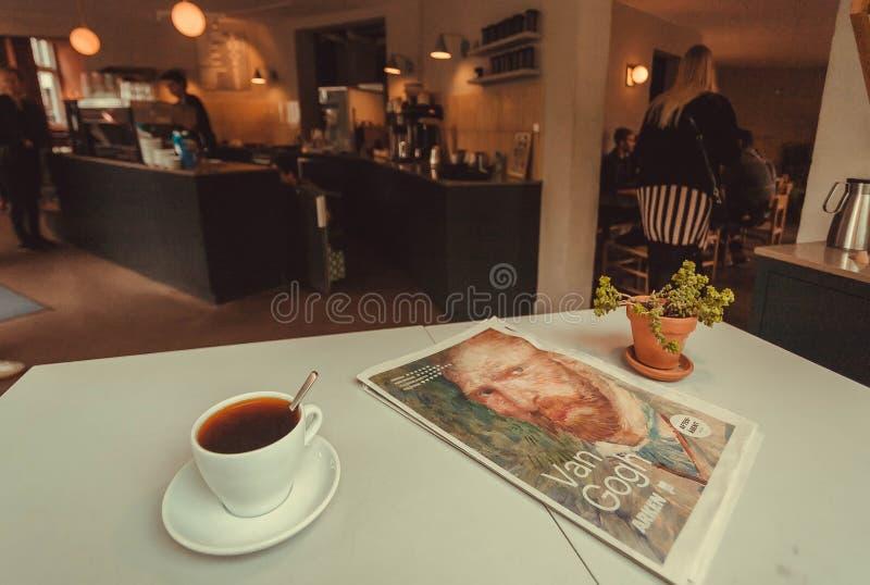 Πρόγευμα με τη μαύρη εφημερίδα πρωινού ράβδων καφέ μέσα στον καφέ πόλεων στοκ φωτογραφία