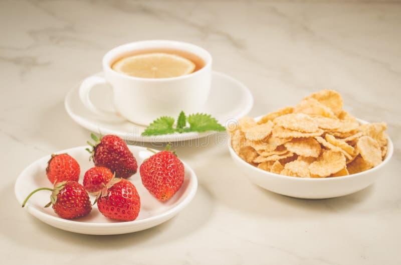 πρόγευμα με τη φράουλα, τις νιφάδες, το μέλι και το τσάι με ένα λεμόνι/το πρόγευμα με τη φράουλα, τις νιφάδες, το μέλι και το τσά στοκ φωτογραφίες με δικαίωμα ελεύθερης χρήσης