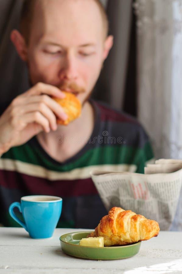 Πρόγευμα με τον καφέ και croissant με το νεαρό άνδρα στο υπόβαθρο στοκ εικόνα με δικαίωμα ελεύθερης χρήσης
