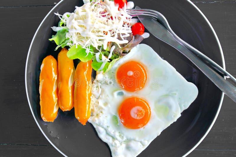 Πρόγευμα με το ζωηρόχρωμες τηγανισμένες χοτ ντογκ αυγό και τη σαλάτα πιάτων στοκ εικόνα