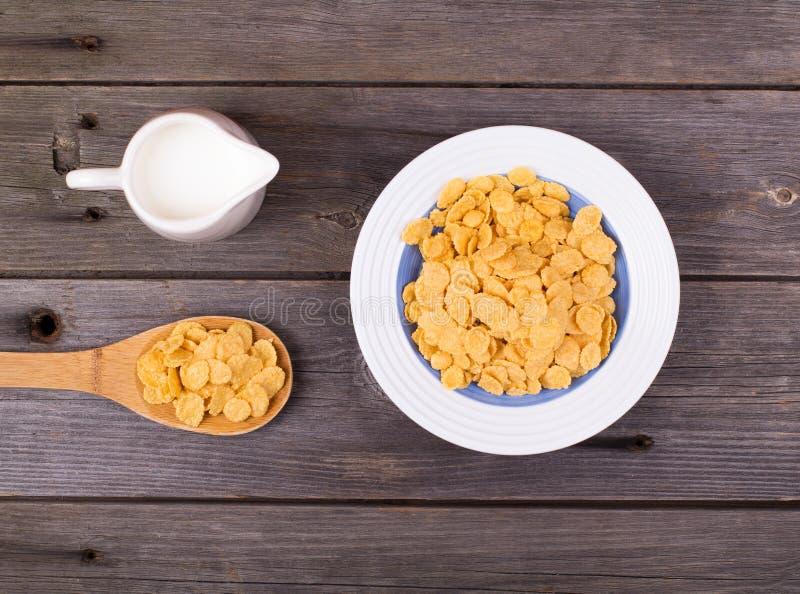 Πρόγευμα: νιφάδες σε ένα πιάτο, γάλα σε μια κανάτα στοκ φωτογραφίες