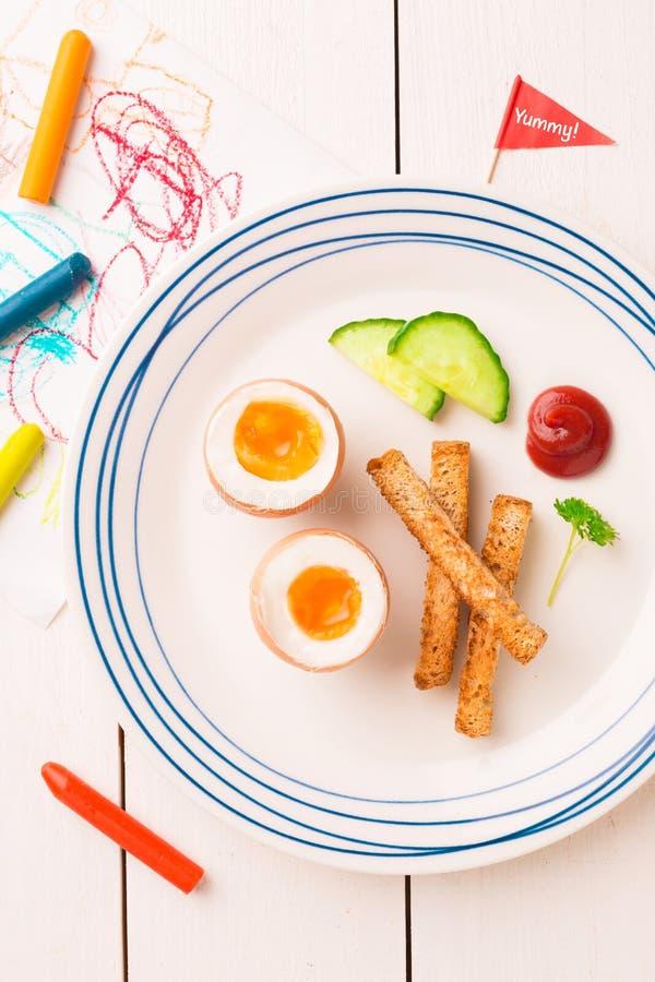 Πρόγευμα παιδιού - αυγά, φρυγανιές, αγγούρι και κέτσαπ στοκ εικόνες