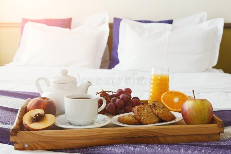 Πρόγευμα που εξυπηρετείται στο κρεβάτι στον ξύλινο δίσκο στοκ εικόνες