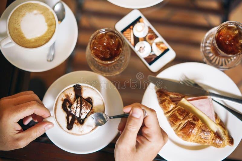 Πρόγευμα πρωινού για δύο: ένας croissant με το ζαμπόν, καφές, ένα αναζωογονώντας ποτό Αρσενικά χέρια που κρατούν ένα φλιτζάνι του στοκ εικόνα