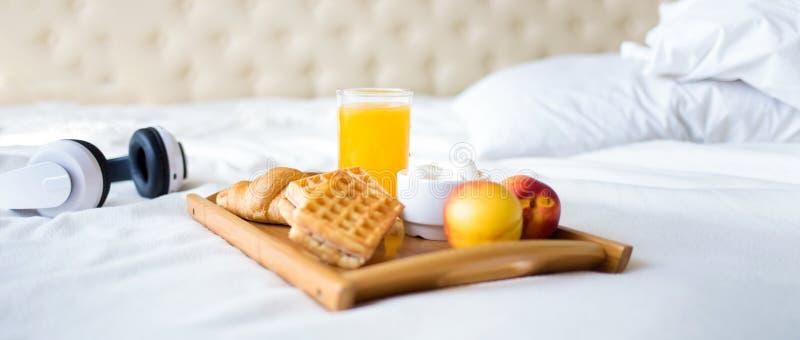 Πρόγευμα πρωινού στο άσπρο κρεβάτι Χυμός βαφλών καφέ Croissant δίσκων στοκ εικόνες