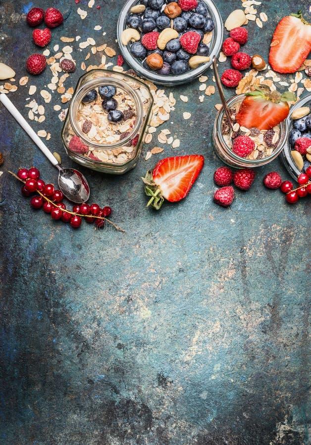 Πρόγευμα στα βάζα Oatmeal με τις φράουλες και άλλα φρέσκα μούρα, καρύδια και σπόροι στο αγροτικό υπόβαθρο, τοπ άποψη στοκ φωτογραφίες με δικαίωμα ελεύθερης χρήσης
