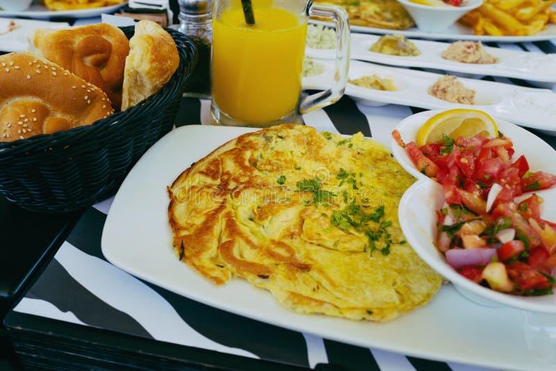 Πρόγευμα στο εστιατόριο με την ομελέτα, τη σαλάτα, το ψωμί και το χυμό από πορτοκάλι στο ύφος instagram στοκ εικόνα