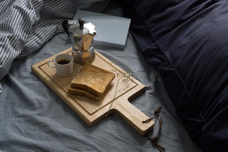 Πρόγευμα στο κρεβάτι, το βιβλίο, Espresso και τη φρυγανιά το πρωί στοκ φωτογραφία