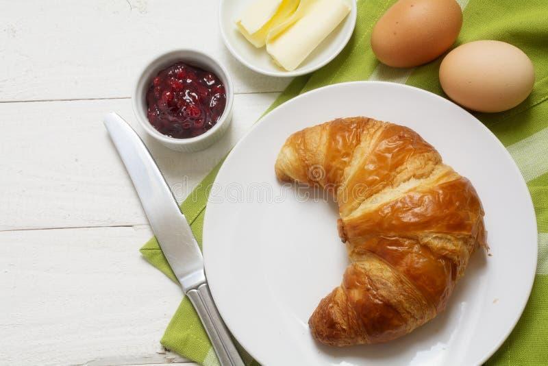 Πρόγευμα της Κυριακής με croissant, μαρμελάδα και αυγό, πράσινη πετσέτα στο άσπρο ξύλο στοκ εικόνα με δικαίωμα ελεύθερης χρήσης