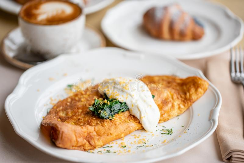 Πρόγευμα Frittata - ιταλική ομελέτα Ομελέτα με τις ντομάτες, το αβοκάντο, το σπανάκι και το μαλακό τυρί Croissants, καφές και στοκ εικόνες με δικαίωμα ελεύθερης χρήσης