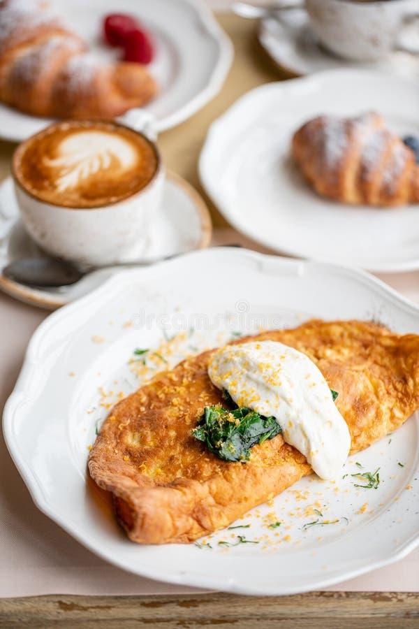 Πρόγευμα Frittata - ιταλική ομελέτα Ομελέτα με τις ντομάτες, το αβοκάντο, το σπανάκι και το μαλακό τυρί Croissants, καφές και στοκ εικόνες