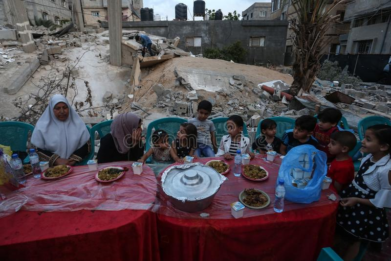 Πρόγευμα Ramadan πέρα από τα ερείπια των σπιτιών που κατεδαφίζονται με τα ισραηλινά πολεμικά αεροσκάφη κατά τη διάρκεια του τελευ στοκ φωτογραφία