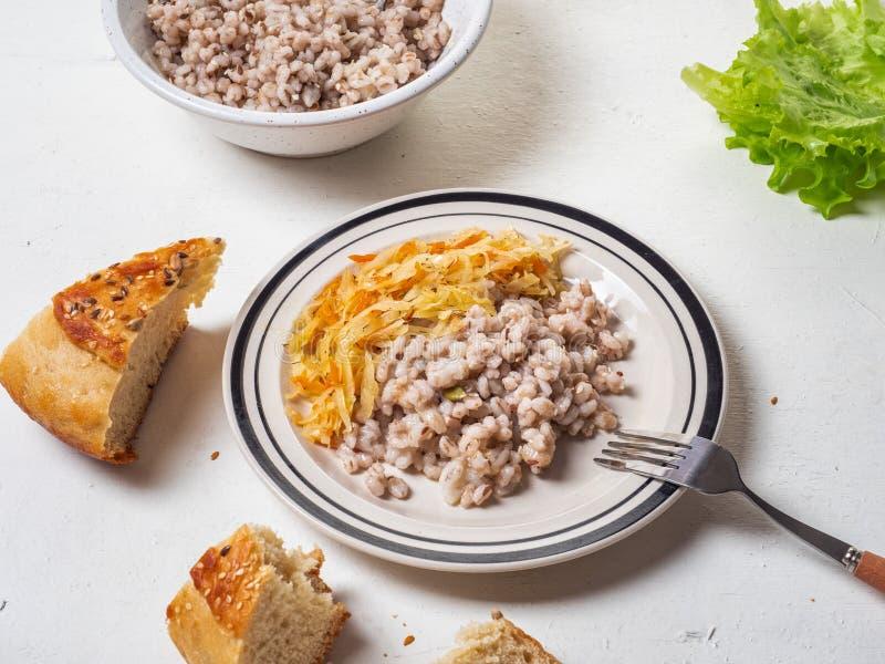 Πρόγευμα Vegan του κριθαριού και μαγειρευμένο λάχανο σε ένα άσπρο πιάτο, κοντινά χοντρά κομμάτια του σπιτικού ψωμιού στοκ φωτογραφία με δικαίωμα ελεύθερης χρήσης
