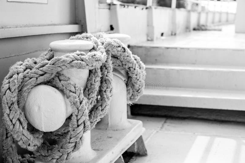 Πρόσδεση Bitts με το άσπρο σχοινί στο μεγάλο σκάφος, γραπτή φωτογραφία στοκ εικόνα