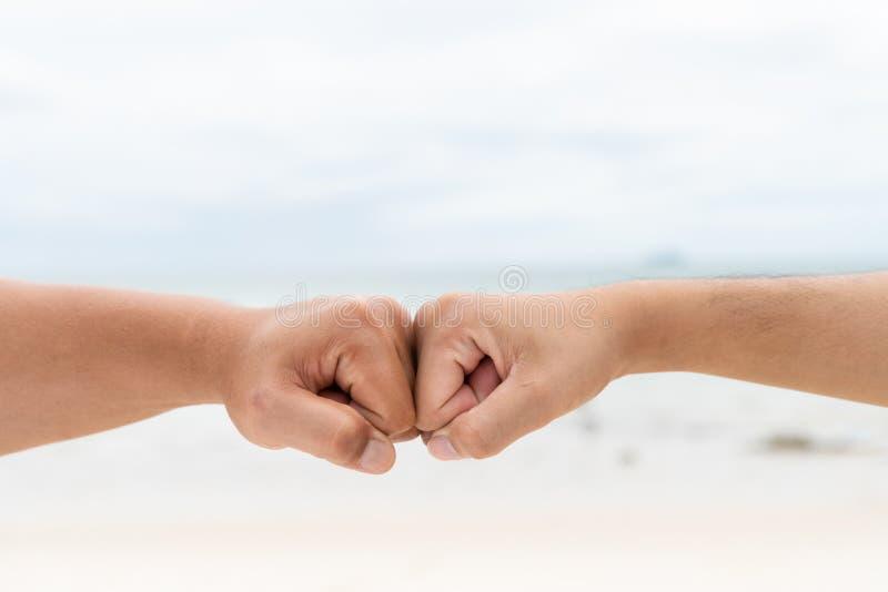 Πρόσκρουση πυγμών χεριών ατόμων μαζί στη θολωμένους θάλασσα και τον ουρανό στοκ φωτογραφία με δικαίωμα ελεύθερης χρήσης