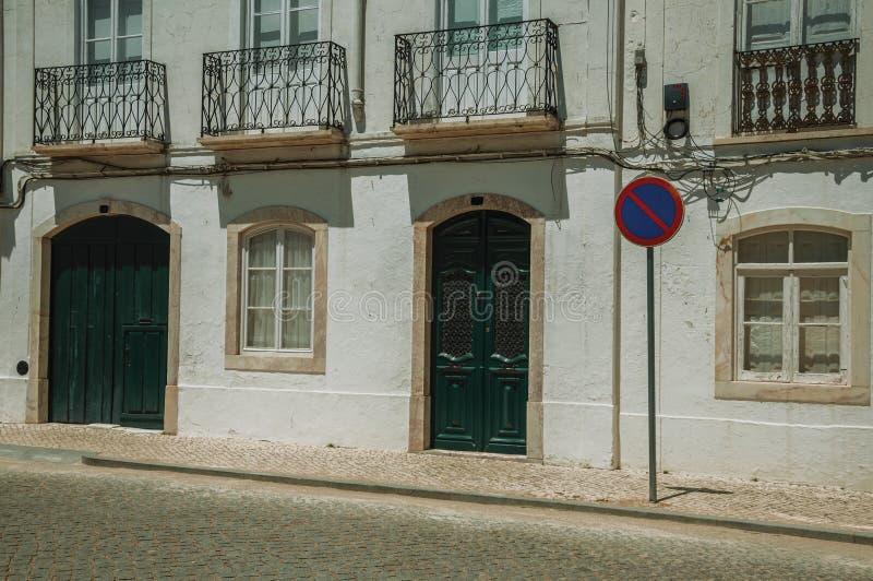 Πρόσοψη μεγάρων με το ραγισμένο τοίχο και ΚΑΝΕΝΑ ΠΕΡΙΜΕΝΟΝΤΑΣ οδικό σημάδι στοκ εικόνα με δικαίωμα ελεύθερης χρήσης