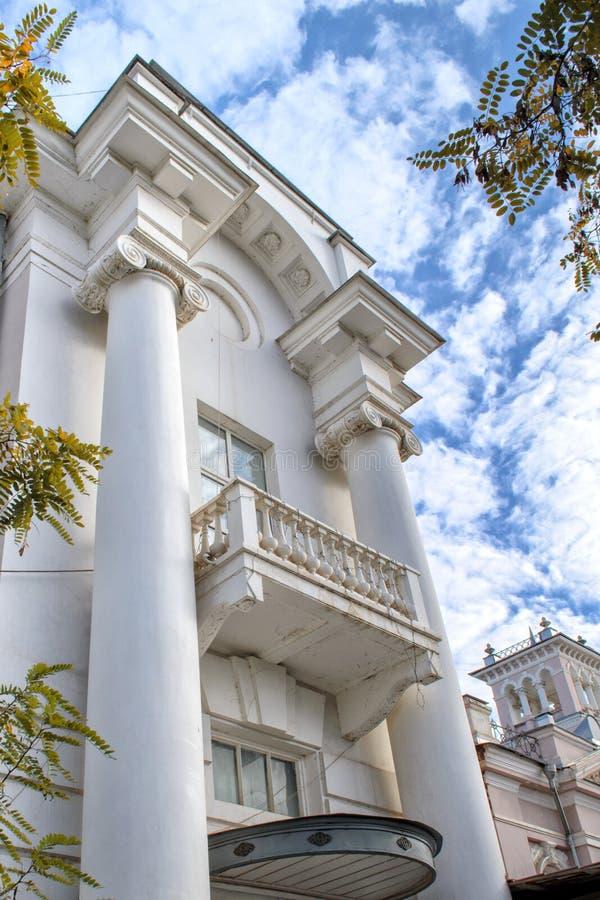 Πρόσοψη της αρχαίας οικοδόμησης του άσπρου χρώματος με δύο άνω και κάτω τελείες και ένα μπαλκόνι στα πλαίσια των άσπρων σύννεφων  στοκ φωτογραφία με δικαίωμα ελεύθερης χρήσης