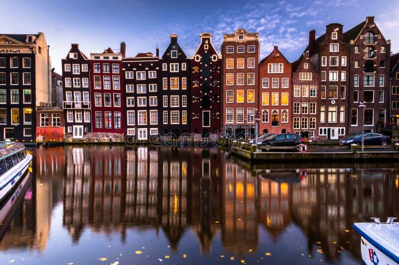 Πρόσοψη της οικοδόμησης του Άμστερνταμ με την αντανάκλαση στο κανάλι, να εξισώσει (μακροχρόνια έκθεση πυροβοληθείσα) στοκ φωτογραφία