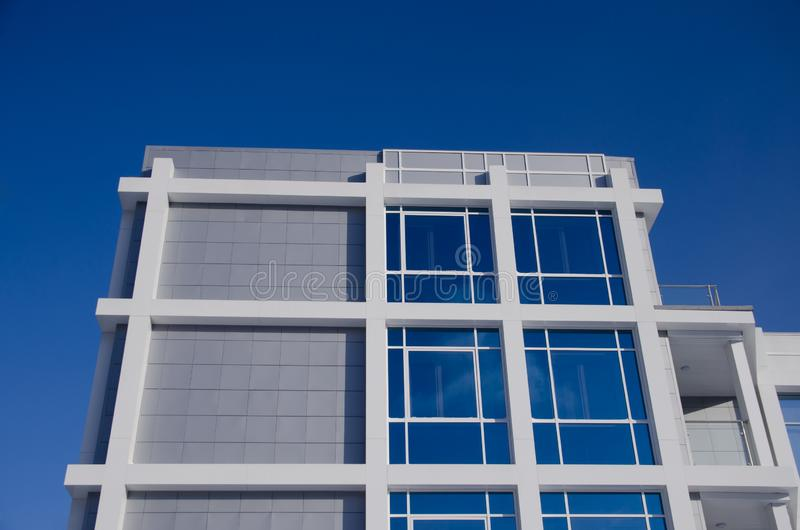 Πρόσοψη του σύγχρονου επιχειρησιακού κτηρίου με τα μεγάλα αντανακλημένα παράθυρα και του μπαλκονιού ενάντια στο μπλε ουρανό στοκ εικόνες με δικαίωμα ελεύθερης χρήσης