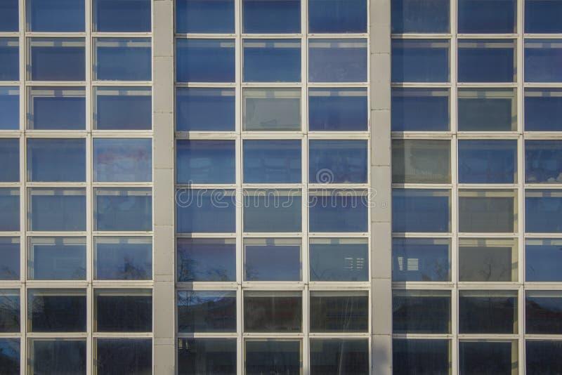 Πρόσοψη του υψηλού σύγχρονου κτηρίου γυαλιού με τα τετραγωνικά παράθυρα και μιας αντανάκλασης του μπλε ουρανού στοκ φωτογραφία