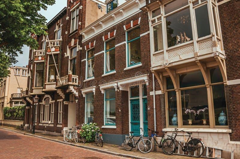 Πρόσοψη των κομψών κτηρίων και των ποδηλάτων τούβλου στην οδό σε μια νεφελώδη ημέρα σε Dordrecht στοκ φωτογραφία με δικαίωμα ελεύθερης χρήσης