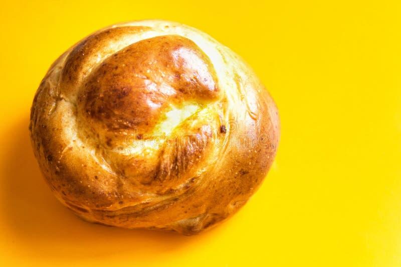 Πρόσφατα κατ' οίκον ψημένο χειροτεχνικό κουλούρι ψωμιού Πάσχας γλυκό στο φωτεινό κίτρινο υπόβαθρο Ζύμη καφέ Πρωί προγευμάτων ψησί στοκ εικόνες